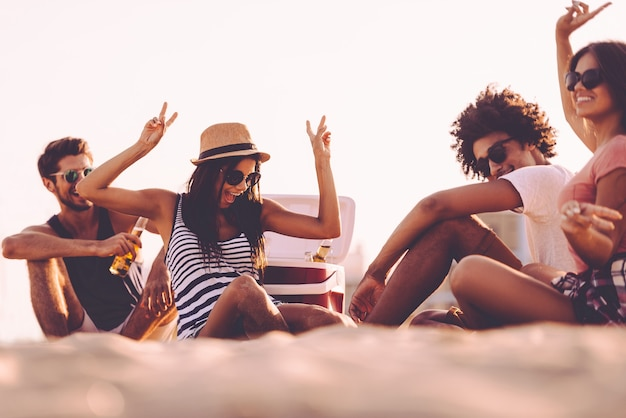 Aproveitando a festa na praia. jovens alegres passando bons momentos juntos enquanto estão sentados na praia bebendo cerveja