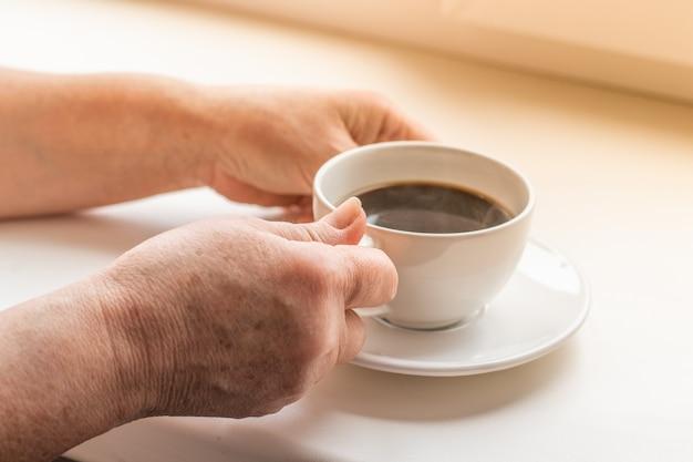 Aproveitando a hora do café em casa. mulher e café nas mãos