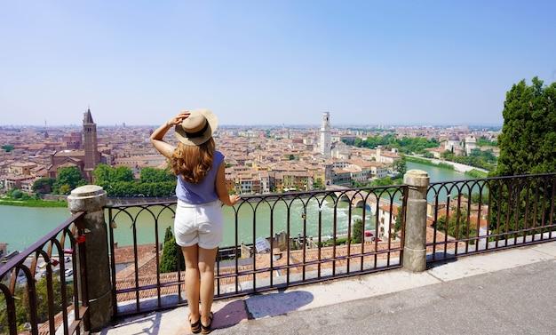 Aproveitando a itália. mulher bonita e elegante no terraço, apreciando a vista da cidade de verona, itália.