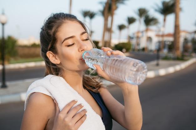 Aproveitando a manhã ensolarada, bebendo água da garrafa com os olhos fechados de uma jovem muito esportiva no treinamento lá fora. treino, cidade tropical, relaxamento, estilo de vida saudável