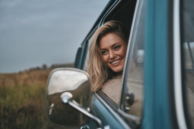 Aproveitando a viagem. mulher jovem e atraente olhando pela janela da van e sorrindo enquanto está sentada no banco do passageiro da frente
