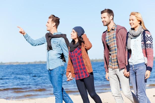 Aproveitando a vida com os melhores amigos. dois lindos casais jovens caminhando juntos pela praia enquanto um homem bonito apontando para longe e sorrindo