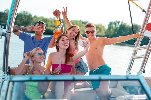 Aproveitando a vida. grupo de amigos alegres bebendo refrigerantes e tirando selfies em um iate olhando diretamente para a câmera