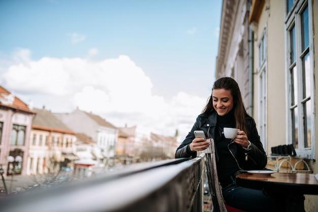 Aproveitando a xícara de café e usando o telefone na varanda no núcleo da cidade velha.
