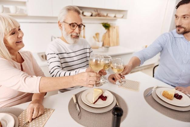Aproveitando as férias em família. casal idoso, otimista e sincero, jantando e aproveitando as férias com o filho maduro, enquanto levanta taças cheias de videira