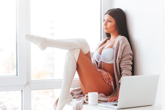 Aproveitando bom dia. mulher jovem e bonita em lingerie e meias brancas com as pernas cruzadas na altura dos joelhos e olhando pela janela em casa