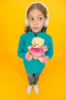 Aproveitando cada nota. educação musical. gosto musical. acessório musical. lazer e diversão. tenho essa sensação. menina com fones de ouvido sem fio de audição de música de brinquedo macio. apaixonado por som estéreo.