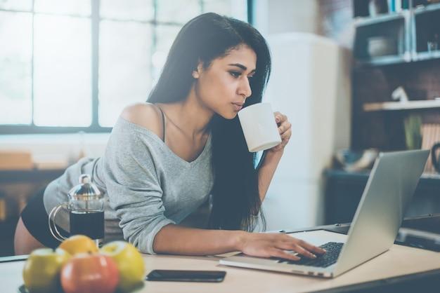 Aproveitando o café em casa. mulher jovem e bonita de raça mista tomando seu café da manhã e olhando para o laptop enquanto se inclina na mesa da cozinha em casa