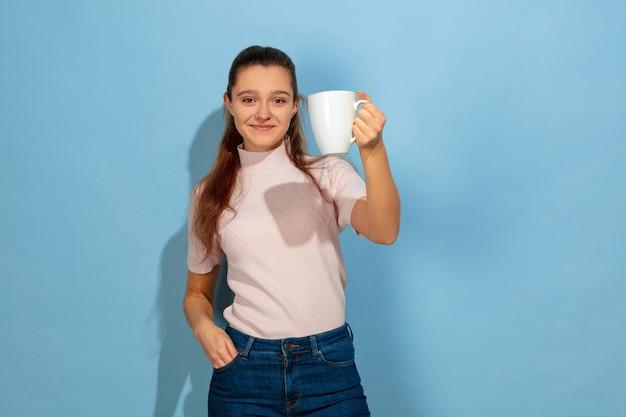 Aproveitando o café, o chá, parece tranquilo. retrato de uma menina adolescente caucasiana sobre fundo azul. bela modelo em moda casual. conceito de emoções humanas, expressão facial, vendas, anúncio. copyspace. parece feliz.