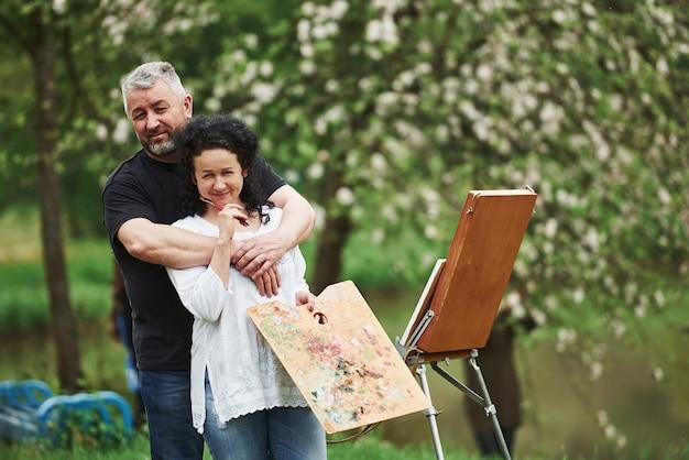 Aproveitando o fim de semana. casal maduro tem dias de lazer e trabalhando na pintura juntos no parque