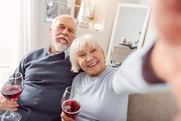 Aproveitando o momento. casal de idosos felizes, sentado no sofá, bebendo vinho, tirando selfies e sorrindo alegremente