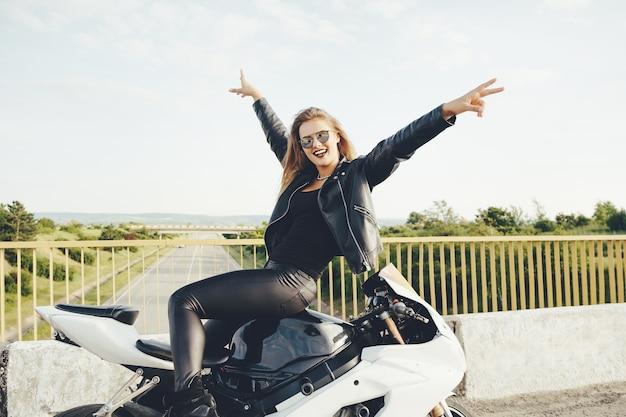 Aproveitando o momento motociclista mulher posando com as mãos para cima