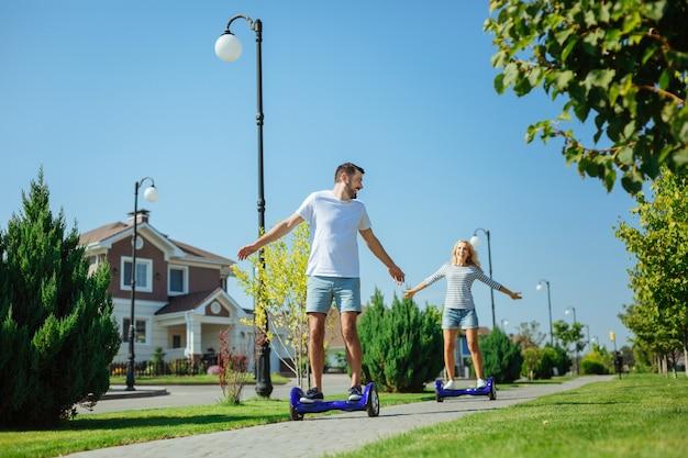 Aproveitando o passeio rápido. casal adorável e otimista andando de pranchas flutuantes um após o outro na calçada em sua rua enquanto espalha as mãos amplamente