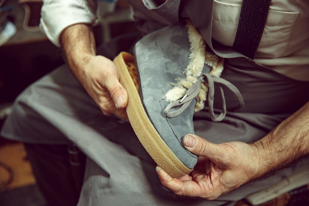 Aproveitando o processo de criação de sapatos feitos sob medida. local de trabalho do designer de calçados. mãos de sapateiro lidando com ferramenta de sapateiro, close-up