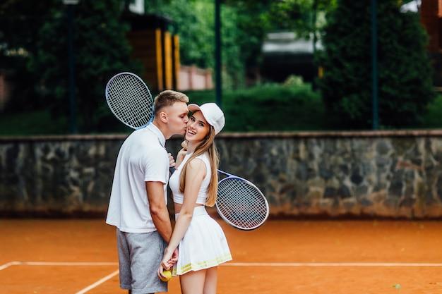 Aproveitando o tempo juntos. a foto da parte traseira, par novo bonito, homem beija sua mulher na corte de tênis com sorriso.