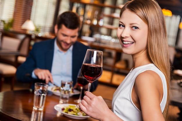 Aproveitando o tempo juntos. mulher jovem e bonita segurando um copo com vinho tinto e sorrindo enquanto está sentada no restaurante com o namorado sentado ao fundo