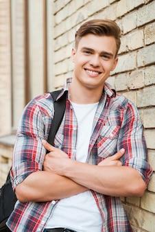 Aproveitando o tempo na faculdade. jovem bonito carregando mochila em um ombro e sorrindo enquanto se inclina para a parede de tijolos