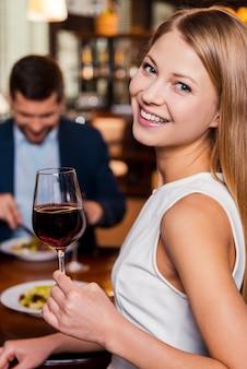 Aproveitando o tempo no restaurante. mulher jovem e bonita segurando um copo com vinho tinto e sorrindo enquanto está sentada no restaurante com o namorado sentado ao fundo