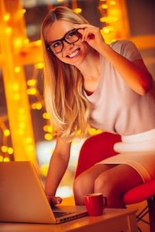 Aproveitando o trabalho até tarde. mulher jovem e bonita em traje esporte fino olhando para a câmera e sorrindo enquanto trabalha no laptop e com luzes de natal ao fundo