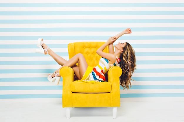 Aproveitando o verão de alegre bela jovem em um vestido colorido, com cabelo longo encaracolado morena relaxando na cadeira amarela na parede branca azul listrada. se divertindo, modelo estiloso, sorrindo.
