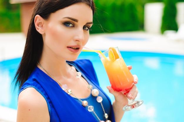 Aproveitando o verão. mulher jovem e bonita a beber cocktails enquanto relaxa perto da piscina