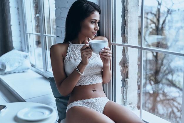 Aproveitando um bom dia em casa. mulher jovem e atraente olhando pela janela e tomando café da manhã enquanto está sentada no parapeito da janela em casa
