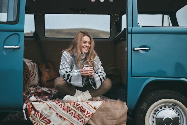Aproveitando um lindo dia. mulher jovem e atraente sorridente segurando uma caneca e desviando o olhar enquanto está sentado dentro da mini van azul estilo retro