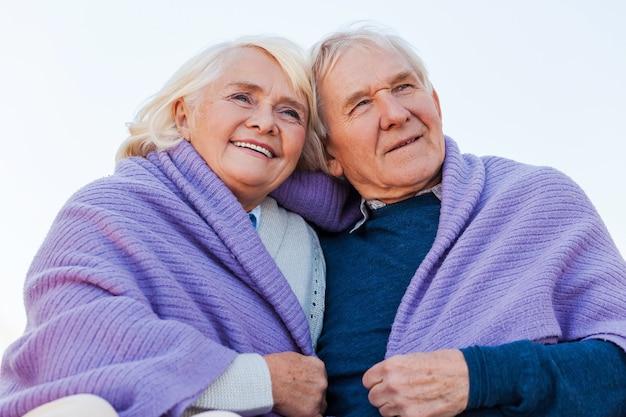 Aproveitando um ótimo dia juntos. vista de baixo ângulo de um feliz casal de idosos se unindo e sorrindo enquanto é coberto por uma manta