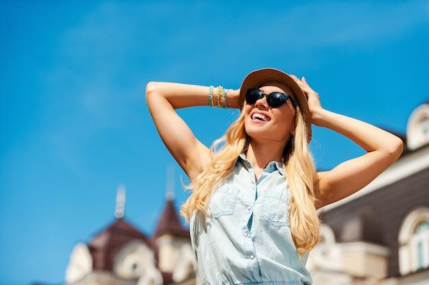 Aproveitando um ótimo dia na cidade. vista de baixo ângulo de uma jovem sorridente, segurando a cabeça nas mãos e olhando para longe ao ar livre