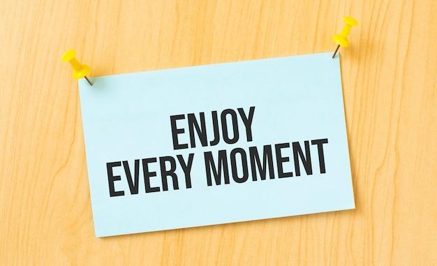 Aproveite cada momento, sinal escrito em nota adesiva fixada na parede de madeira