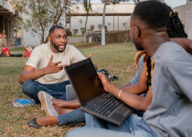 Aproxime os alunos aprendendo ao ar livre com um laptop