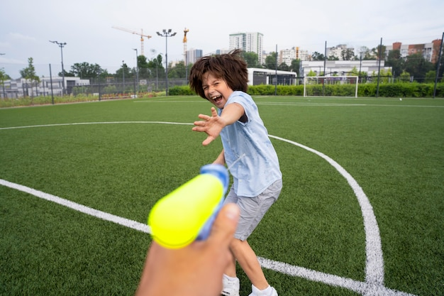 Aproxime-se das crianças brincando com uma pistola d'água no campo