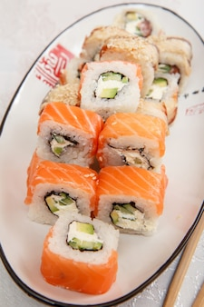 Aproxime-se do uramaki filadélfia. rolinhos de sushi com salmão, nori, arroz, queijo philadelphia, pedaços de abacate e pepino no prato de cerâmica. culinária japonesa. profundidade superficial de campo.