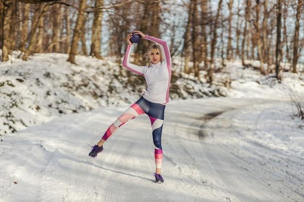 Apta a desportista fazendo exercícios com bola de fitness na natureza em dia de inverno nevado. vida saudável, equipamentos de fitness, fitness de inverno