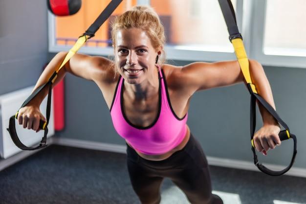 Apta a jovem loira exercitando malhando com alças de fitness trx no ginásio. treino físico para corpo feminino