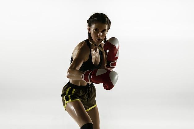 Apta a mulher caucasiana no boxe sportswear isolado na parede branca. novato boxeador caucasiano feminino treinando e praticando em movimento e ação. esporte, estilo de vida saudável, conceito de movimento.