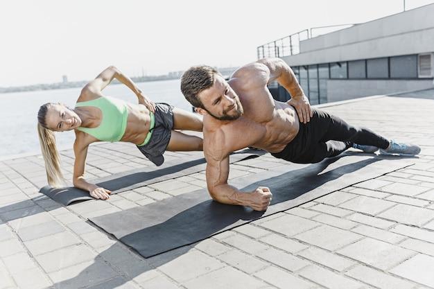 Apta a mulher de aptidão e o homem fazendo exercícios de aptidão ao ar livre no fundo da cidade. a melhor musculação abdominal do mundo. modelos de esportes femininos e masculinos, exercitando-se no verão pela manhã.
