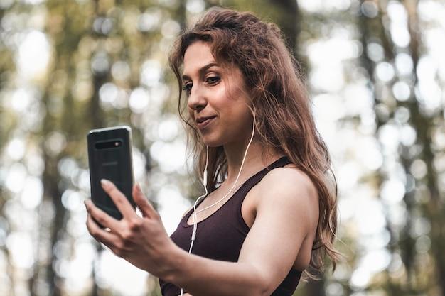 Apta a mulher fazendo uma selfie após seu exercício ao ar livre. retrato de uma jovem e bonita garota de esportes tomando uma selfie na floresta de pinheiros.