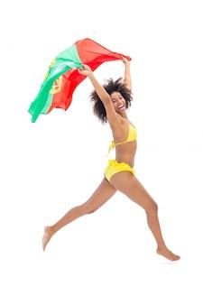 Apta garota de biquíni amarelo segurando a bandeira de portugal rindo de câmera