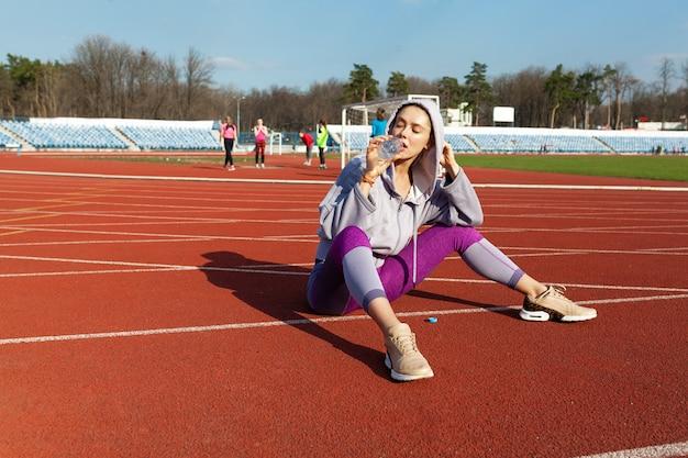 Apta garota desportiva relaxante depois da corrida