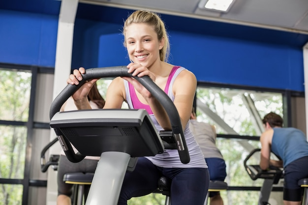 Apta mulher fazendo bicicleta ergométrica no ginásio