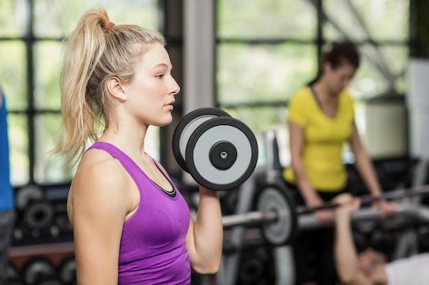 Apta mulher levantando halteres no ginásio crossfit