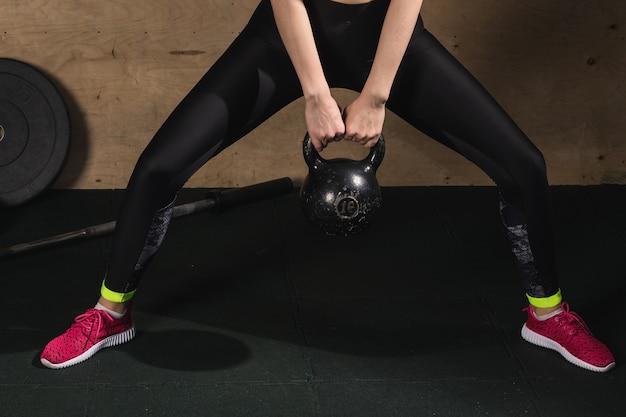 Apta mulher levantando sino de chaleira peso pesado no ginásio