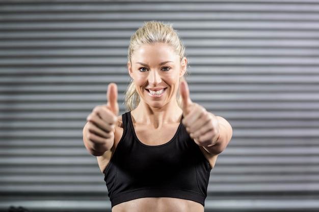 Apta mulher mostrando os polegares no ginásio crossfit