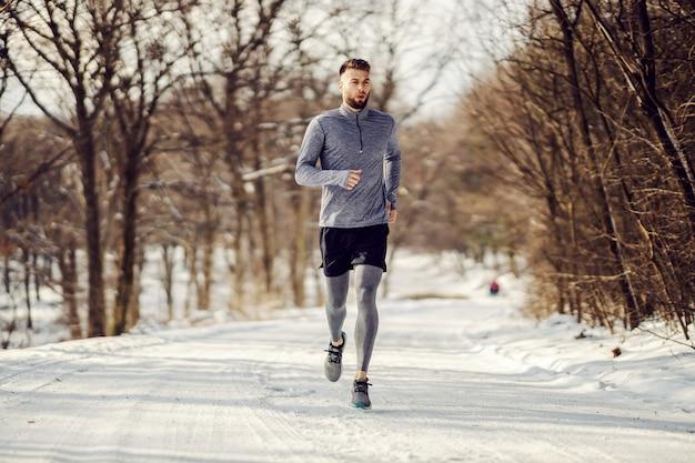 Apta o desportista correndo na natureza na neve no inverno. estilo de vida saudável, fitness de inverno, clima frio