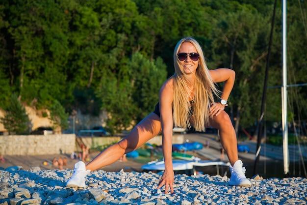 Aptidão ao ar livre de mulher esbelta em forma bonita em um dia ensolarado de verão. fazendo exercícios ao ar livre, conceito de estilo de vida ativo e saudável. agachamentos de pulo. sinta-se feliz