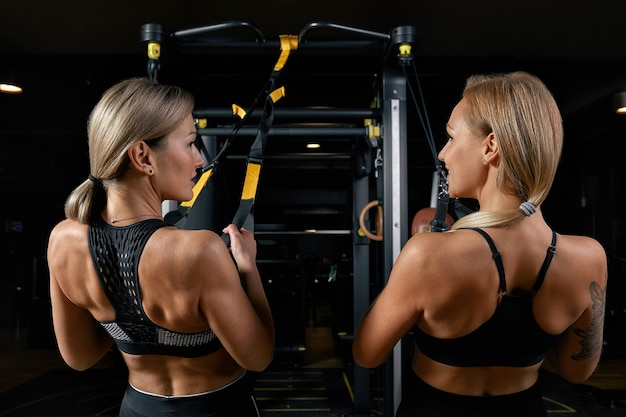 Aptidão brutal duas amigas com um músculo no ginásio. esportes e fitness - conceito de estilo de vida saudável. mulher de fitness no ginásio.