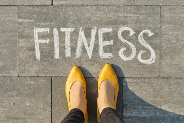 Aptidão da palavra escrita na calçada cinza com pernas de mulher