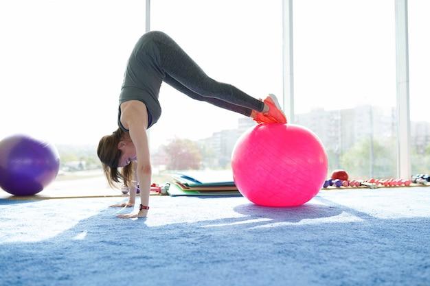 Aptidão de mulher. linda mulher caucasiana sênior fazendo exercício com bola no ginásio