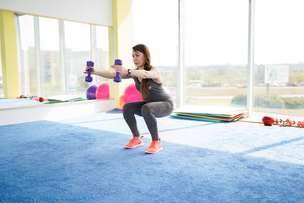 Aptidão de mulher. linda mulher caucasiana sênior fazendo exercício no ginásio